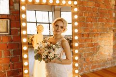 In the Studio, the bride in a white dress stands near the mirror. Beautiful bride stands near the mirror and looks into her reflection,blonde royalty free stock photos