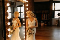 The bride in a white dress stands near the mirror and prepare for the ceremony. Beautiful bride stands near the mirror and looks into her reflection royalty free stock photo