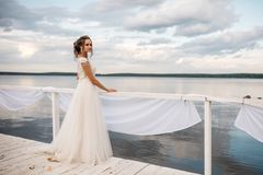 Beautiful bride stands on the pier. Water and cloudy sky on the background stock photo