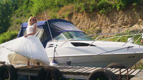 Beautiful bride stands, posing on the yacht on sunny day sailboat. Slow motion. HD stock video footage