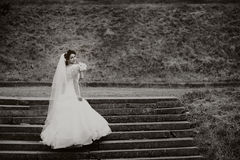 Beautiful bride stands on the stairs. Black and white Royalty Free Stock Images