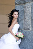 A beautiful bride by the stone wall Royalty Free Stock Image