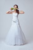 Beautiful bride studio full length portrait. Beautiful bride holding bouquet in her mouth Stock Images