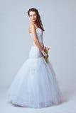 Beautiful bride studio full length portrait. Beautiful bride holding bouquet studio full length portrait, toned image Royalty Free Stock Photos