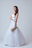 Beautiful bride studio full length portrait. Beautiful bride holding bouquet studio full length portrait, toned image Royalty Free Stock Images