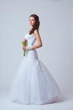 Beautiful bride studio full length portrait. Beautiful bride holding bouquet studio full length portrait, toned image Stock Images