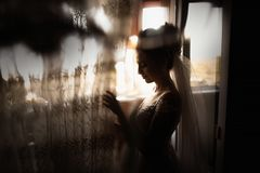 Beautiful bride style. Wedding girl stand in luxury wedding dress near window royalty free stock photos