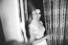 Beautiful bride style. Wedding girl stand in luxury wedding dress near window. Black and white stock photo