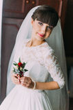 Beautiful bride with stylish hairlock posing when holding cute floral boutonniere in dressing room Royalty Free Stock Images