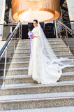 Beautiful bride in stylsh dress stands alone on stairs indoor Stock Images