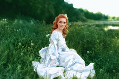 Beautiful bride in summer green park. Girl in vintage dress sits near river. Stock Images