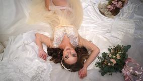 Beautiful bride is surrounded by wedding dresses, look straight into the camera, big beautiful eyes. Beautiful bride in one peignoir lies surrounded by wedding stock video