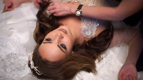 Beautiful bride is surrounded by wedding dresses, make-up artist corrects hair. Beautiful bride in one peignoir lies surrounded by wedding dresses. High angle stock footage