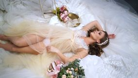Beautiful bride is surrounded by wedding dresses. Beautiful bride in one peignoir lies surrounded by wedding dresses. High angle view. ery model. Around the stock footage
