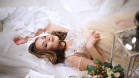 Beautiful bride is surrounded by wedding dresses. Beautiful bride in one peignoir lies surrounded by wedding dresses. High angle view. Fashion wedding. Medium stock video