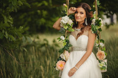 Beautiful bride is swinging on a swing Stock Photography