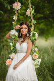 Beautiful bride is swinging on a swing Royalty Free Stock Photo