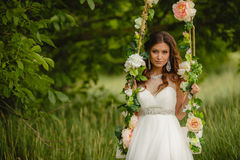 Beautiful bride is swinging on a swing Stock Image