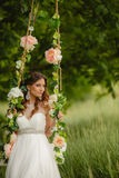 Beautiful bride is swinging on a swing Royalty Free Stock Photos