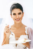 Beautiful bride taste a wedding cake Royalty Free Stock Image