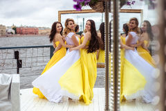 Beautiful Bride and two bridesmaids together on a summer terrace a sea restaurant. Beautiful Bride and two bridesmaids in yellow similar dresses together on a Stock Images