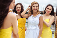 Beautiful Bride and two bridesmaids together on a summer terrace a sea restaurant. Beautiful Bride and two bridesmaids in yellow similar dresses together on a Stock Photos