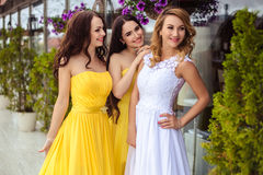 Beautiful Bride and two bridesmaids together on a summer terrace a sea restaurant. Beautiful Bride and two bridesmaids in yellow similar dresses together on a Stock Image