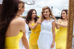 Beautiful Bride and two bridesmaids together on a summer terrace a sea restaurant. Beautiful Bride and two bridesmaids in yellow similar dresses together on a Stock Photo