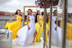 Beautiful Bride and two bridesmaids together on a summer terrace a sea restaurant. Beautiful Bride and two bridesmaids in yellow similar dresses together on a Royalty Free Stock Photo