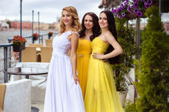 Beautiful Bride and two bridesmaids together on a summer terrace a sea restaurant. Beautiful Bride and two bridesmaids in yellow similar dresses together on a Royalty Free Stock Image