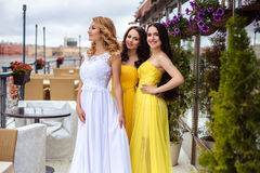Beautiful Bride and two bridesmaids together on a summer terrace a sea restaurant. Beautiful Bride and two bridesmaids in yellow similar dresses together on a Stock Photography