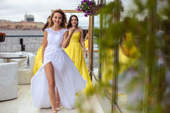 Beautiful Bride and two bridesmaids together on a summer terrace a sea restaurant. Beautiful Bride and two bridesmaids in yellow similar dresses together on a Royalty Free Stock Images