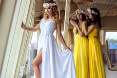 Beautiful Bride and two bridesmaids in yellow similar dresses together in a sea restaurant Royalty Free Stock Images