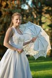 Beautiful bride with umbrella in the park Stock Images