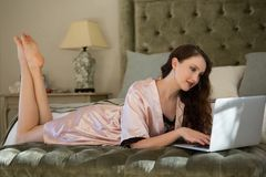 Beautiful bride using laptop while relaxing on bed Stock Images