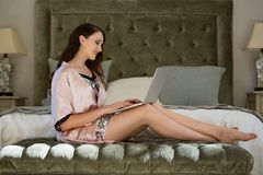 Beautiful bride using laptop while sitting on bed at home Royalty Free Stock Photo