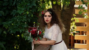 Beautiful bride in a vintage dress with colored bouquet of fresh flowers. Looking at the camera and smiling. stock video
