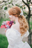 Beautiful bride in a vintage wedding dress posing in a blooming apple garden Stock Photo
