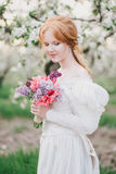 Beautiful bride in a vintage wedding dress posing in a blooming apple garden Stock Photography