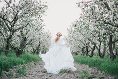 Beautiful bride in a vintage wedding dress posing in a blooming apple garden. Spring mood. Young woman in a white vintage dress Royalty Free Stock Photo