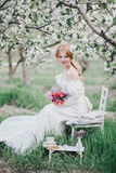 Beautiful bride in a vintage wedding dress posing in a blooming apple garden Royalty Free Stock Image