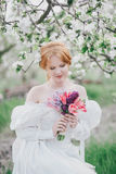 Beautiful bride in a vintage wedding dress posing in a blooming apple garden. Spring mood Royalty Free Stock Photo