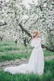 Beautiful bride in a vintage wedding dress posing in a blooming apple garden. Spring mood Stock Photo