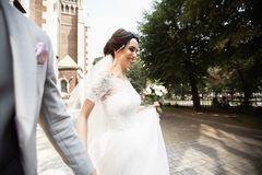 Beautiful bride walks with his groom near old christian church royalty free stock image