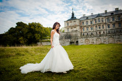 Beautiful bride walks next to castle Royalty Free Stock Photo