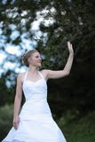 Beautiful bride waving and smiling. While outdoors Royalty Free Stock Image