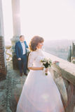Beautiful bride wearing white dress posing on old balcony, groom in background Royalty Free Stock Image