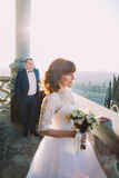 Beautiful bride wearing white dress posing on old balcony, groom in background Stock Photos