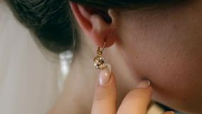 Beautiful bride wears an earring in the mirror stock video