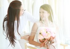 Beautiful bride wears veil holding a soft focus bouquet making e stock photography